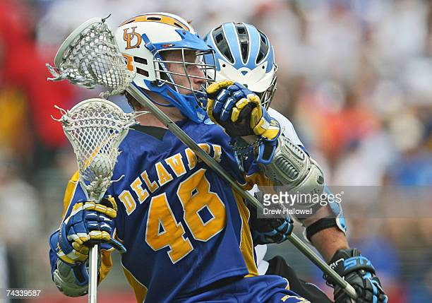 Curtis Dickson of the University of Delaware gets checked from behind by defenseman Matt Bocklet of Johns Hopkins University at MT Bank Stadium May...