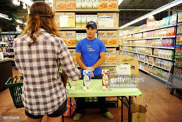 Curtis Gardner talks to a customer as he gives out samples of three new soy milks from Earth Balance at the Whole Foods in Boulder on Monday August...