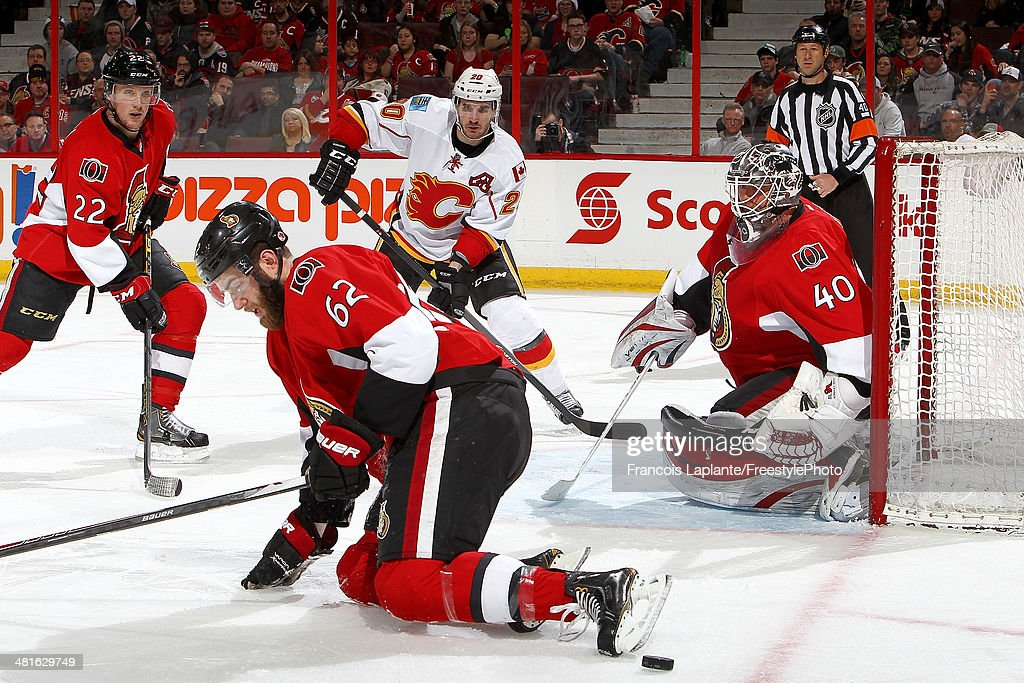 Curtis Glencross #20 of the Calgary Flames takes position as Eric Gryba #62 of the Ottawa Senators blocks a shot as Robin Lehner #40 and Erik Condra #22 defends during an NHL game at Canadian Tire Centre on March 30, 2014 in Ottawa, Ontario, Canada.