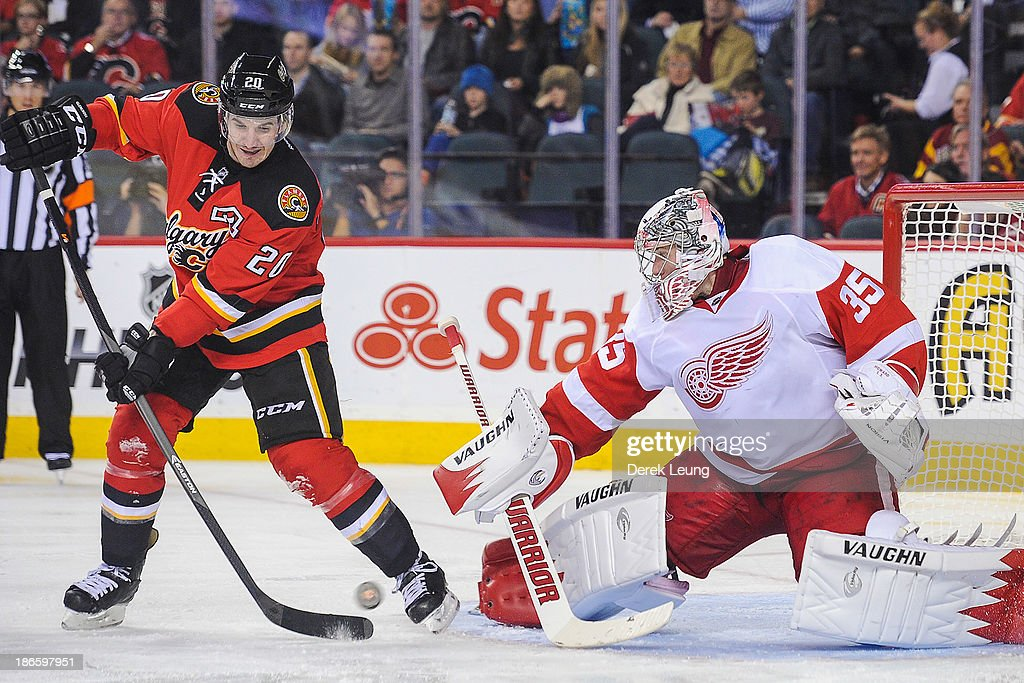 Curtis Glencross #20 of the Calgary Flames tries to redirect the puck into the net of Jimmy Howard #35 of the Detroit Red Wings during an NHL game at Scotiabank Saddledome on November 1, 2013 in Calgary, Alberta, Canada. The Red Wings defeated the Flames 4-3.