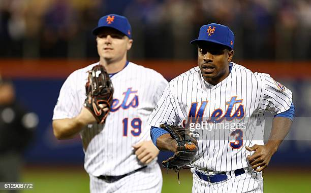 Curtis Granderson and Jay Bruce of the New York Mets react after Granderson caught a ball hit by Brandon Belt of the San Francisco Giants for an out...