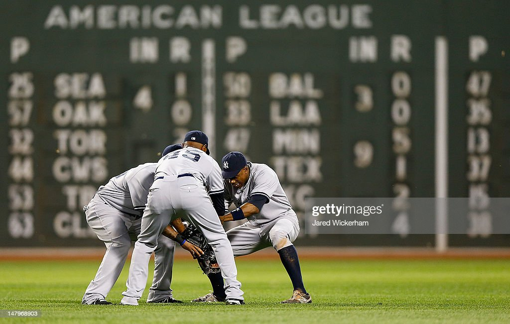 Curtis Granderson #14, Dewayne Wise #45, and Darnell McDonald of the New York Yankees celebrate in center field following their win against the Boston Red Sox during the game on July 6, 2012 at Fenway Park in Boston, Massachusetts.