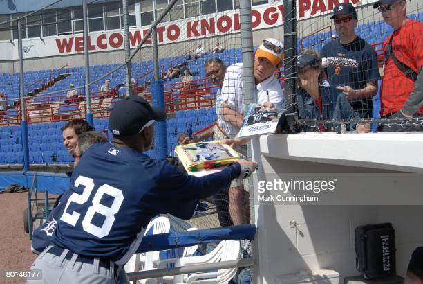 Curtis Granderson of the Detroit Tigers signs autographs for fans before the spring training game against the Toronto Blue Jays at Knology Park in...