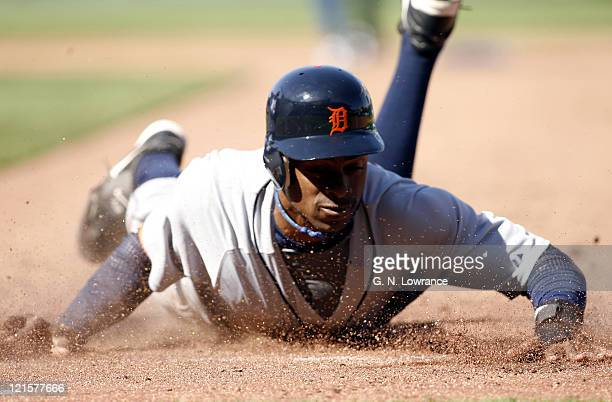 Curtis Granderson of the Detroit Tigers slides back into first base to avoid a tag during action on opening day against the Kansas City Royals at...