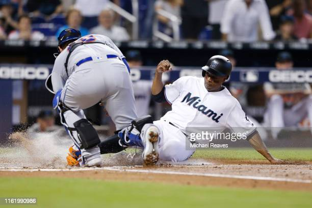Curtis Granderson of the Miami Marlins is tagged out at home by Wilson Ramos of the New York Mets second inning at Marlins Park on July 14 2019 in...