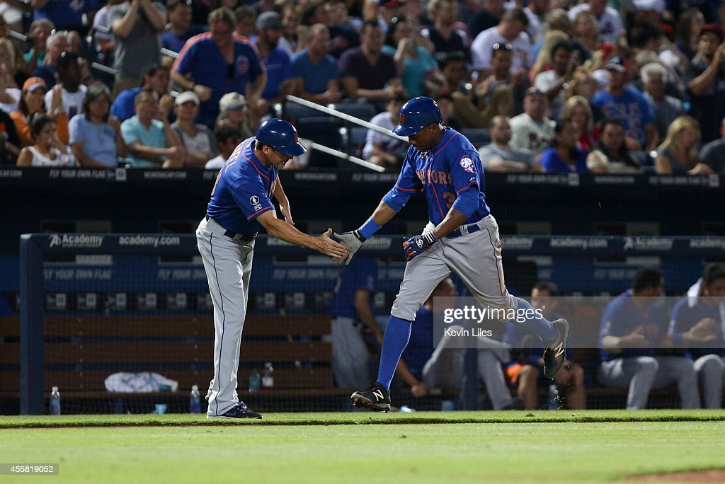 Curtis Granderson #3 of the New York Mets is congratulated by third base coach Tim Teufel (18) during the 8th inning after hitting a home run against the Atlanta Braves at Turner Field on September 20, 2014 in Atlanta, Georgia.