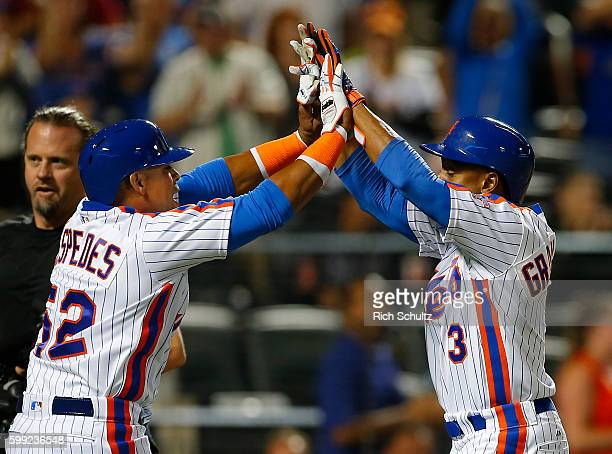 Curtis Granderson of the New York Mets is congratulated by Yoenis Cespedes after Granderson's two run home run against the Washington Nationals...