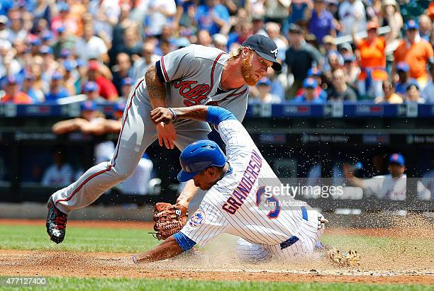 Curtis Granderson of the New York Mets is safe at home ahead of the tag from Mike Foltynewicz of the Atlanta Braves as he scores a first inning run...