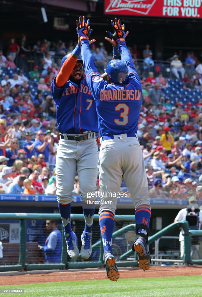 Curtis Granderson #3 of the New York Mets jumps as he high fives Jose Reyes #7 after hitting a two-run home run in the fifth inning during a game against the Philadelphia Phillies at Citizens Bank Park on August 13, 2017 in Philadelphia, Pennsylvania. The Mets won 6-2.