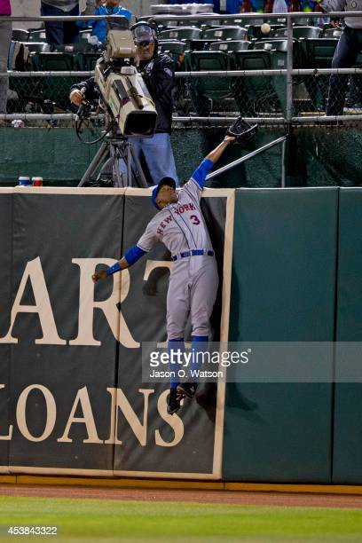 Curtis Granderson of the New York Mets leaps for but is unable to catch a ball hit for a two run home run by Josh Reddick of the Oakland Athletics...