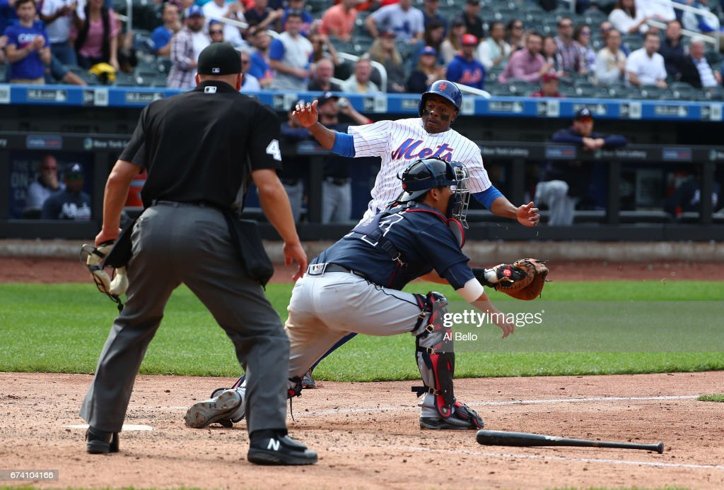 Curtis Granderson #3 of the New York Mets scores a run against Kurt Suzuki #24 of the Atlanta Braves in the ninth inning during their game at Citi Field on April 27, 2017 in New York City.