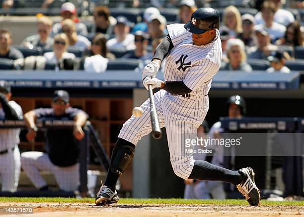 Curtis Granderson of the New York Yankees hits a solo home run in the fourth inning against the Detroit Tigers at Yankee Stadium on April 29 2012 in...