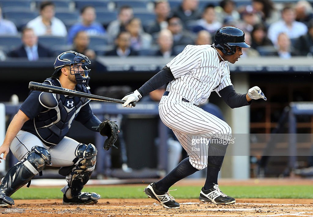 Curtis Granderson #14 of the New York Yankees hits into a double play to end the first inning as Kelly Shoppach #7 of the Seattle Mariners catches on May 14, 2013 at Yankee Stadium in the Bronx borough of New York City.