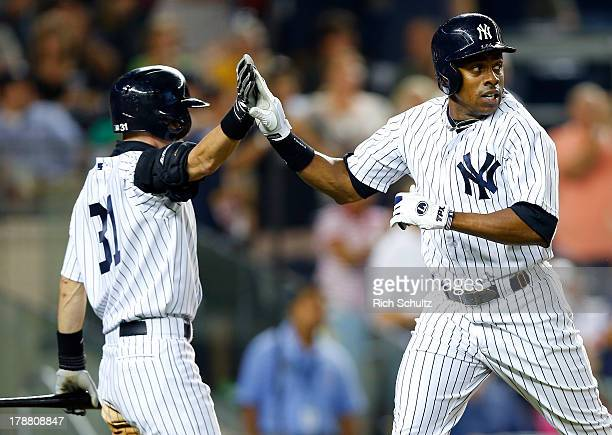Curtis Granderson of the New York Yankees is congratulated by teammate Ichiro Suzuki after scoring on a double by Mark Reynolds in the fifth inning...