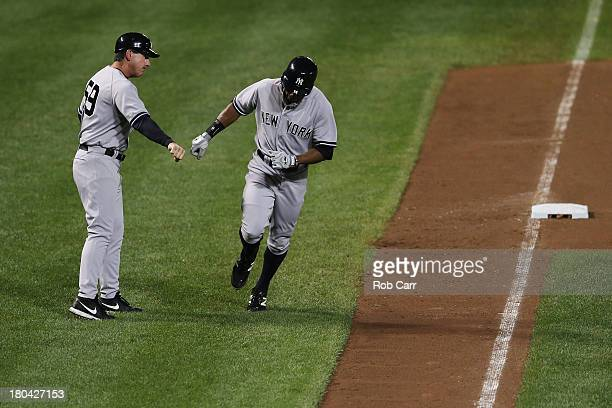 Curtis Granderson of the New York Yankees is congratulated by third base coach Rob Thomson after hitting a solo home run against the Baltimore...