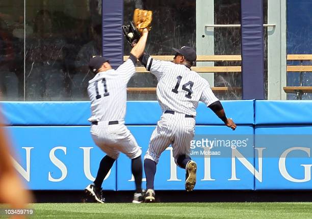 Curtis Granderson of the New York Yankees makes a fourth inning catch on a ball hit by Jhonny Peralta of the Detroit Tigers as he collides with...