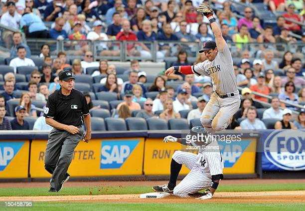 Curtis Granderson of the New York Yankees slides safely under third baseman Nick Punto of the Boston Red Sox as he jumps to catch a high throw in the...