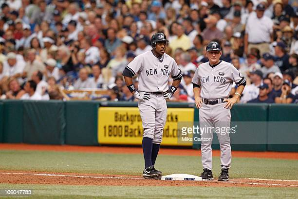 Curtis Granderson of the New York Yankees talks with first base coach Mick Kelleher at first base during the game between the New York Yankees and...