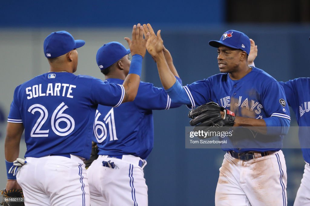 Curtis Granderson #18 of the Toronto Blue Jays celebrates their victory with Yangervis Solarte #26 during MLB game action against the Chicago White Sox at Rogers Centre on April 3, 2018 in Toronto, Canada.