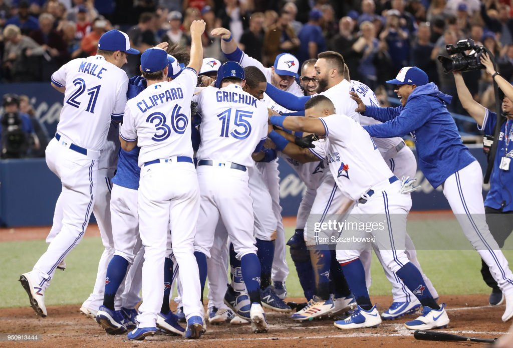 Curtis Granderson #18 of the Toronto Blue Jays is congratulated by teammates after hitting a game-winning solo home run in the tenth inning during MLB game action against the Boston Red Sox at Rogers Centre on April 24, 2018 in Toronto, Canada.