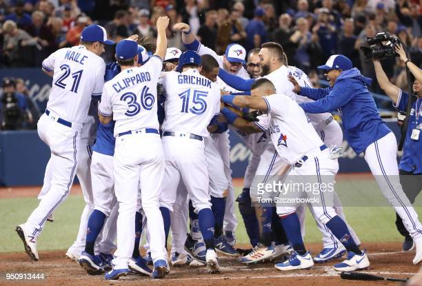 Curtis Granderson of the Toronto Blue Jays is congratulated by teammates after hitting a gamewinning solo home run in the tenth inning during MLB...