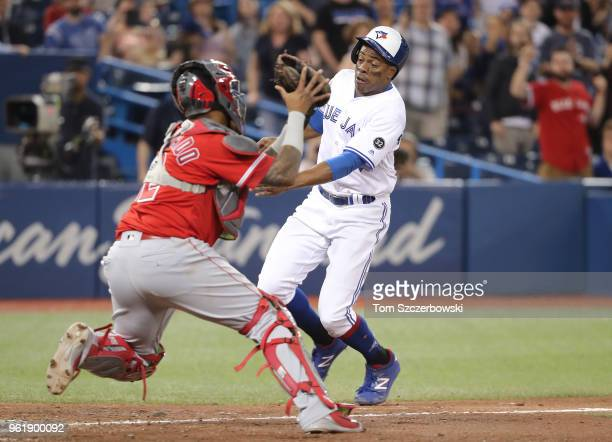 Curtis Granderson of the Toronto Blue Jays is tagged out at home plate by Martin Maldonado of the Los Angeles Angels of Anaheim in the ninth inning...