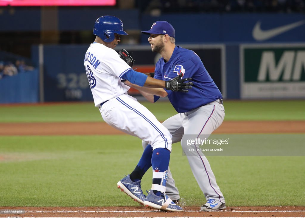 Curtis Granderson #18 of the Toronto Blue Jays is tagged out by Chris Martin #31 of the Texas Rangers in the eighth inning during MLB game action at Rogers Centre on April 27, 2018 in Toronto, Canada.