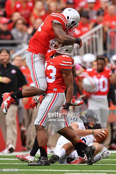 Curtis Grant of the Ohio State Buckeyes and Darron Lee of the Ohio State Buckeyes celebrate after Lee sacked quarterback Colin Reardon of the Kent...