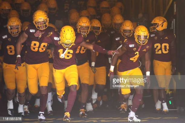Curtis Hodges Aashari Crosswell and Evan Fields of the Arizona State Sun Devils lead teammates out onto the field before the NCAAF game against the...
