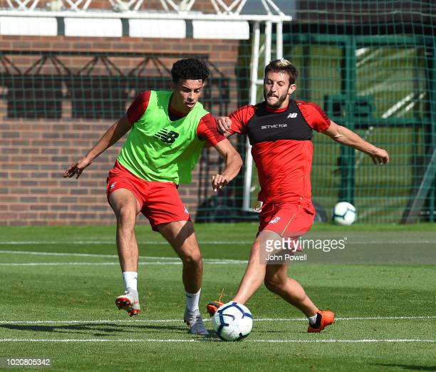 Curtis Jones and Adam Lallana of Liverpool during a training session at Melwood Training Ground on August 21 2018 in Liverpool England