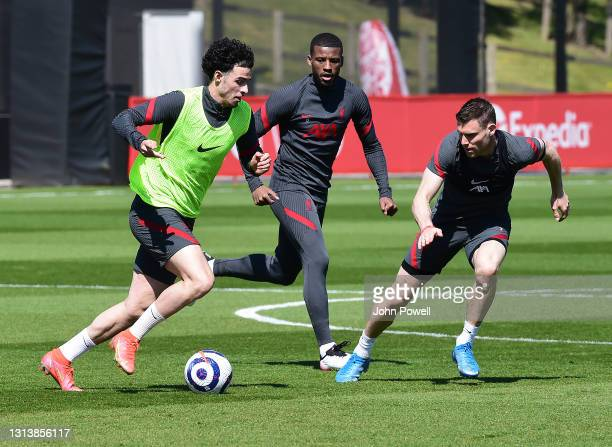 Curtis Jones and James Milner of Liverpool during a training session at AXA Training Centre on April 22, 2021 in Kirkby, England.