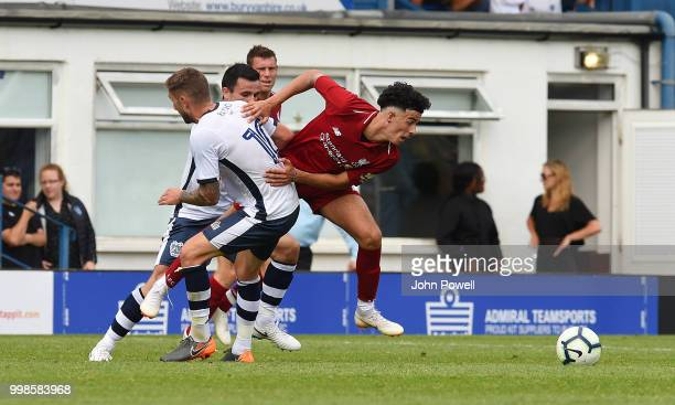 Curtis Jones of Liverpool competes with Danny Mayor of Bury during the PreSeason friendly match between Bury and Liverpool at Gigg Lane on July 14...