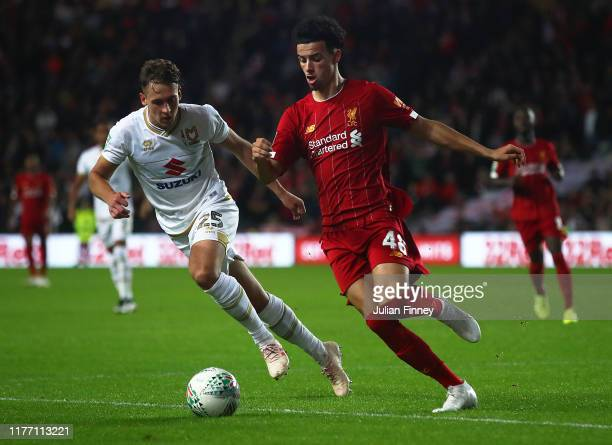 Curtis Jones of Liverpool in action with Callum Brittain of MK Dons during the Carabao Cup Third Round match between MK Dons and Liverpool at Stadium...
