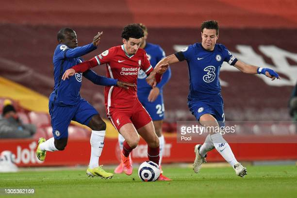 Curtis Jones of Liverpool is challenged by N'Golo Kante of Chelsea and Cesar Azpilicueta of Chelsea during the Premier League match between Liverpool...
