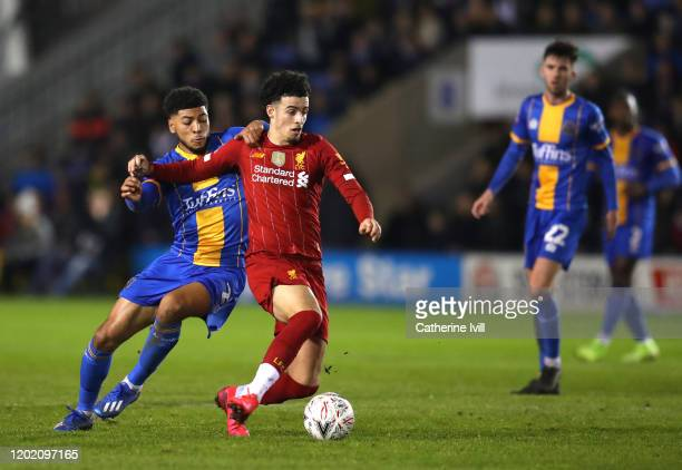 Curtis Jones of Liverpool is tackled by Josh Laurent of Shrewsbury Town during the FA Cup Fourth Round match between Shrewsbury Town and Liverpool at...
