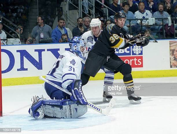 Curtis Joseph and Bryan Berard of the Toronto Maple Leafs skate against Matthew Barnaby of the Pittsburgh Penguins during the 1999 Quarter Finals of...