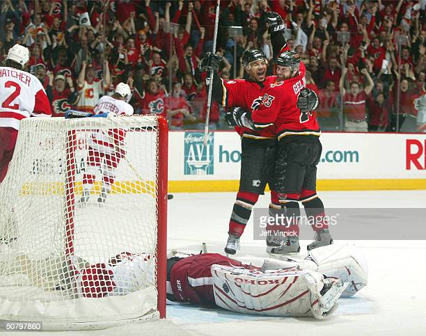 Curtis Joseph of the Detroit Red Wings lays dejected in his crease as Martin Gelinas of the Calgary Flames celebrates his overtime gamewinning goal...