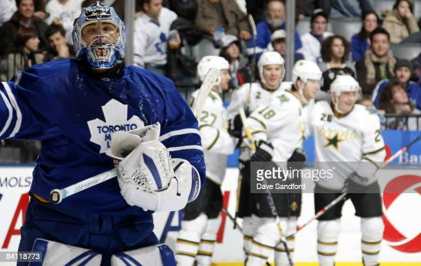 Curtis Joseph of the Toronto Maple Leafs stands in the crease as members of the Dallas Stars celebrate their 8th goal during their NHL game at the...