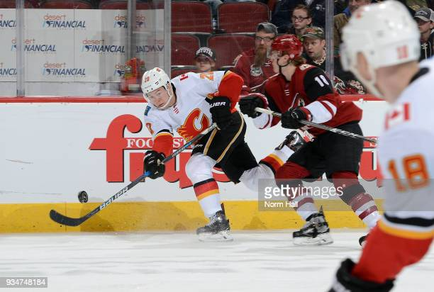 Curtis Lazar of the Calgary Flames passes the puck as Christian Dvorak of the Arizona Coyotes defends during the second period at Gila River Arena on...