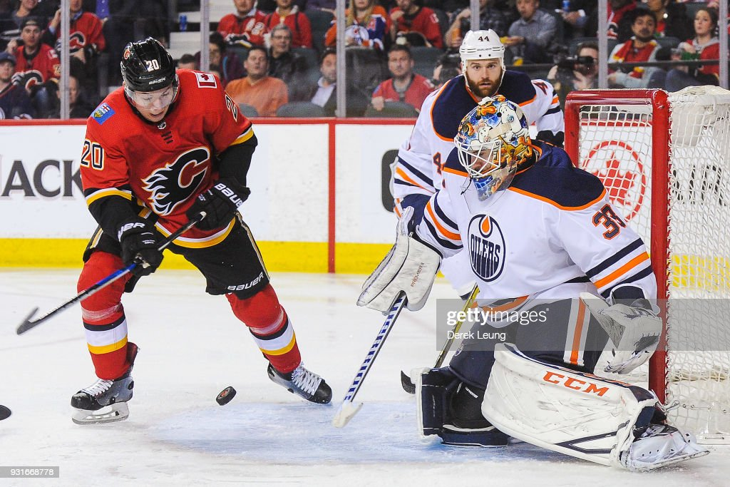 Curtis Lazar #20 of the Calgary Flames takes a shot on Cam Talbot #33 of the Edmonton Oilers during an NHL game at Scotiabank Saddledome on March 13, 2018 in Calgary, Alberta, Canada.