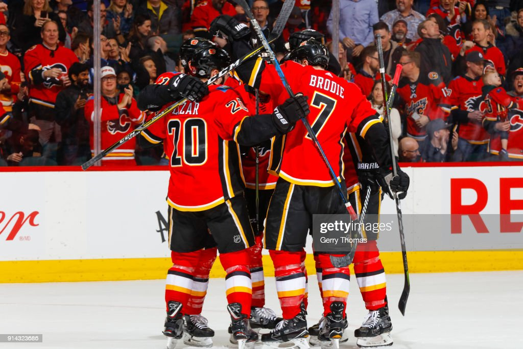 Curtis Lazar #20, TJ Brodie #7 and teammates of the Calgary Flames celebrate in an NHL game on February 1, 2018 at the Scotiabank Saddledome in Calgary, Alberta, Canada.