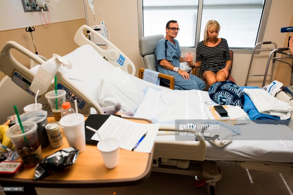 Curtis Leoni, who was shot in the leg at the Route 91 Harvest country music festival on October 1, 2017 when a mass murderer opened fire on the crowd killing 58 people and injuring almost 500, sits with his girlfriend Robin Davis as he recuperates October 5, 2017 at Desert Springs Hospital Medical Center in Las Vegas, Nevada. / AFP PHOTO / Robyn Beck