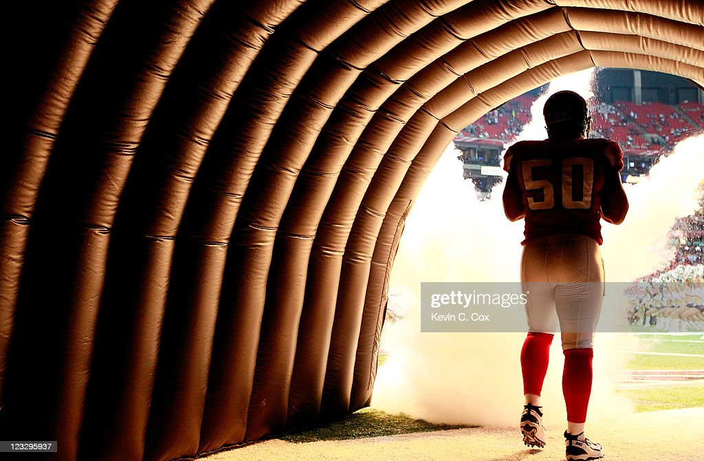 Curtis Lofton #50 of the Atlanta Falcons runs out of the tunnel during player introductions before facing the Baltimore Ravens at Georgia Dome on September 1, 2011 in Atlanta, Georgia.