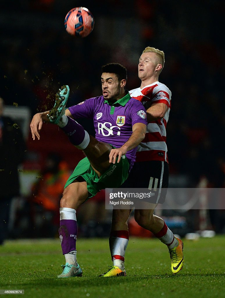 Curtis Main (R) of Doncaster Rovers challenges Derrick Williams of Bristol City during the FA Cup Third Round match between Doncaster Rovers and Bristol City at Keepmoat Stadium on January 3, 2015 in Doncaster, England.