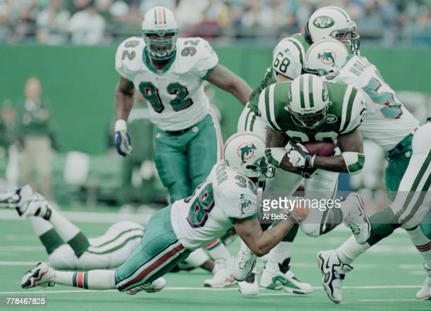 Curtis Martin Running Back for the New York Jets tries to run the ball as Defensive Back Calvin Jackson of the Miami Dolphins makes a block during...