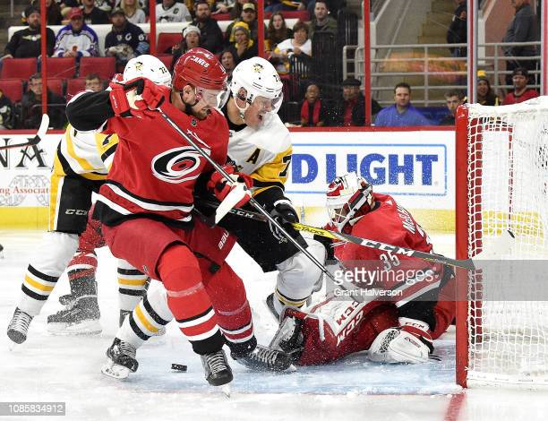 Curtis McElhinney and Calvin de Haan of the Carolina Hurricanes defend a shot by Evgeni Malkin of the Pittsburgh Penguins during the third period...
