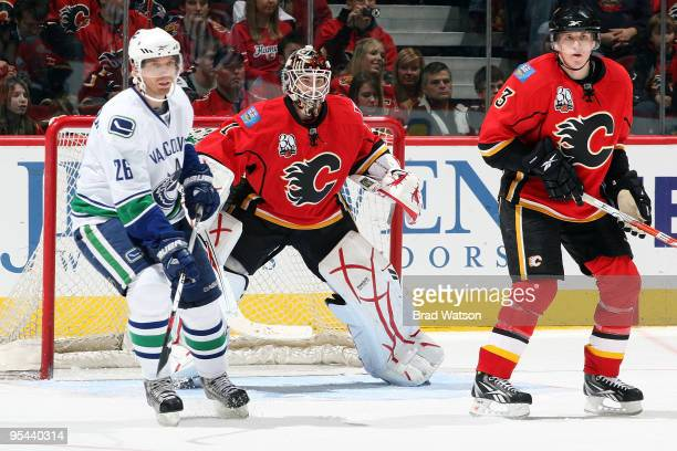 Curtis McElhinney and Dion Phaneuf of the Calgary Flames skate against Mikael Samuelsson of the Vancouver Canucks on December 27 2009 at Pengrowth...