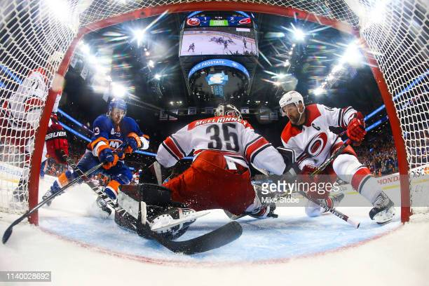 Curtis McElhinney and Justin Williams of the Carolina Hurricanes battle for the loose puck against Mathew Barzal of the New York Islanders during...