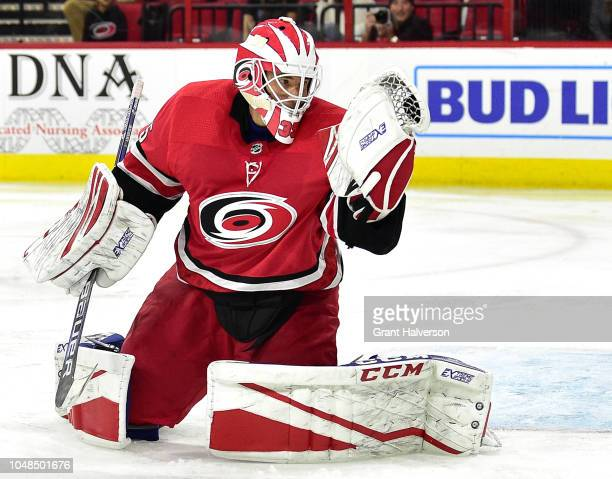Curtis McElhinney of the Carolina Hurricanes checks to make sure the puck is in his glove after making a save against the Vancouver Canucks during...