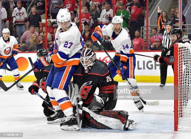 Curtis McElhinney of the Carolina Hurricanes pushes Anders Lee of the New York Islanders out of the crease during the third period of Game Three of...